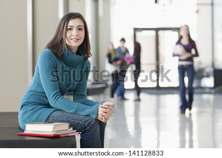 Asian American student seated at table with books in library - stock photo