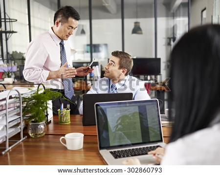 asian and caucasian businesspeople having a discussion in office of a multinational company. - stock photo