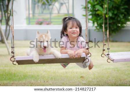 Asian baby  baby on swing with siberian husky puppy - stock photo
