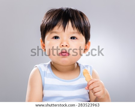 Asian baby boy eat with his biscuit - stock photo