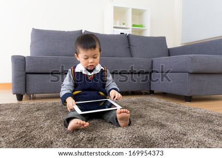 Asian baby boy using tablet at home - stock photo