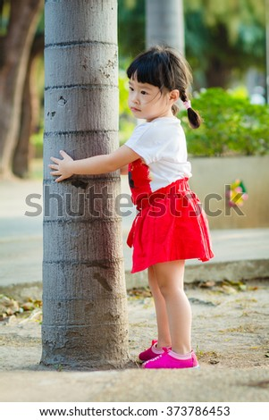 Asian baby cute girl with curly hair in the park - stock photo