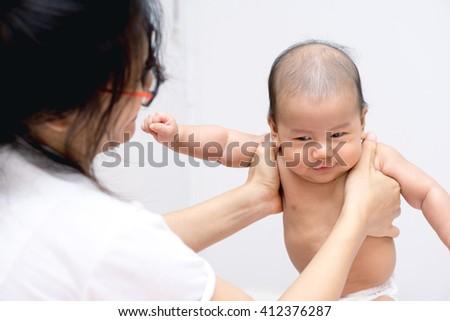 Asian baby  enjoy playing with mother hand - stock photo