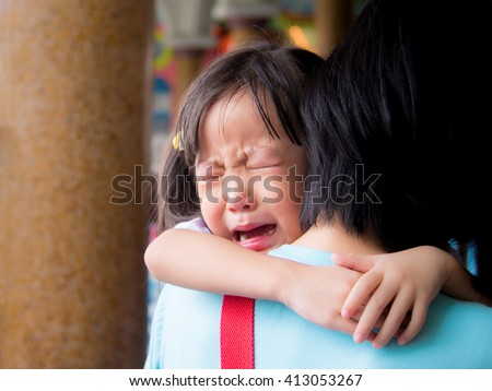 Asian baby girl hugging her mother crying - stock photo