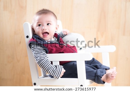 Asian baby in the room. Looking up with surprised expression. - stock photo