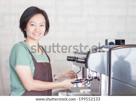 Asian barista smiling and making cup of coffee, stock photo - stock photo