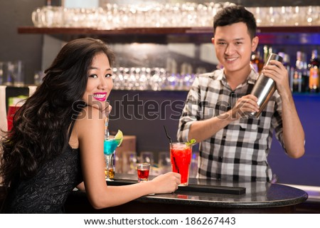 Asian barmen serving drinks to the woman - stock photo