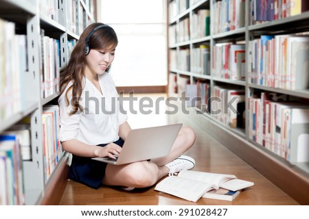 Asian beautiful female student studying in library with laptop - stock photo