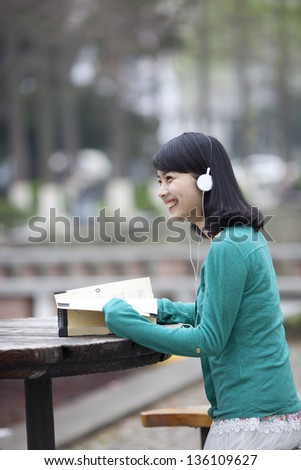 Asian beautiful student reading book in campus with earphone - stock photo