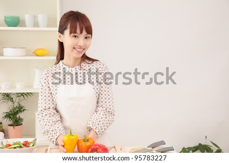 Asian beautiful woman with a smile is in preparation for cooking in the kitchen. - stock photo