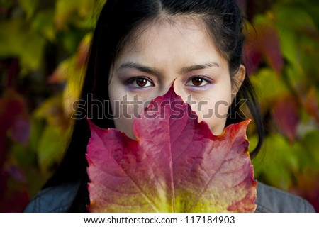 asian beauty behind a colorful maple leaf - stock photo