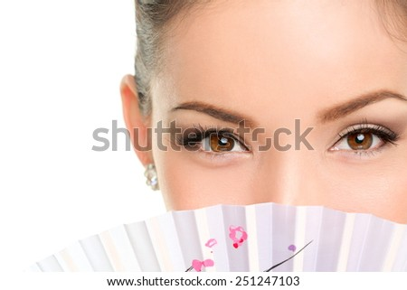 Asian beauty eyes - makeup woman looking with oriental fan. Mysterious chinese lady showing eyeliner and mascara hiding face behind accessory. - stock photo