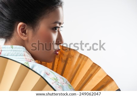 Asian beauty. Rear view of attractive Asian woman wearing Japanese kimono and holding two traditional hand fans while standing against white background with copy space - stock photo