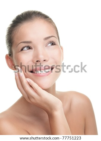 Asian beauty skin care woman smiling close-up. Beautiful young woman touching her face looking to the side. Isolated on white background. Mixed race Asian / Caucasian model. - stock photo