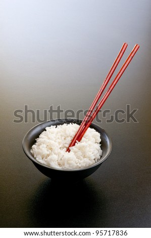 Asian black bowl with rice and red sticks - stock photo