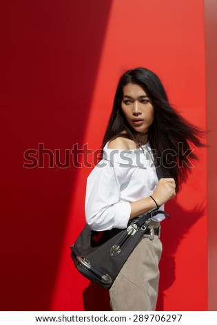 Asian black hair model at the outdoor in city,against red wall - stock photo