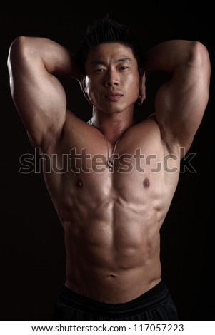 Asian Body Builder Posing flexing looking at the camera - stock photo