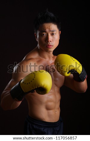 Asian boxer in his attacking stance with yellow gloves - stock photo
