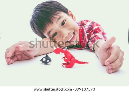Asian boy create and show his toys from play dough, on white background. Strengthen the imagination of child. Vintage style. Cross process. - stock photo
