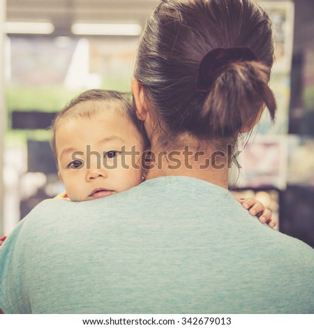 Asian boy crying on mother shoulder, warm retro style - stock photo