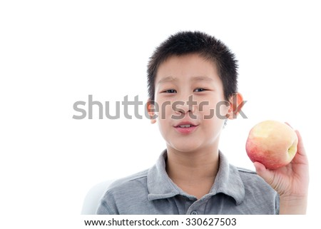 Asian boy eating a red apple isolated on white background - stock photo