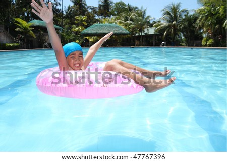 asian boy enjoying on a swimming pool - stock photo