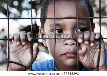 Asian boy from impoverished area, behind and clinging to fence in the Philippines. - stock photo