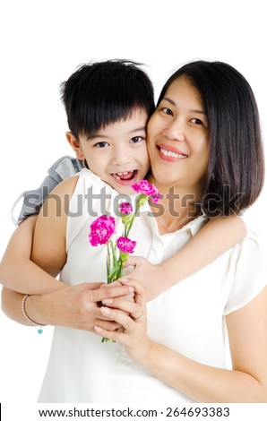 Asian boy giving carnation flower to his mother on mothers day - stock photo