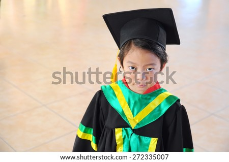Asian boy in graduation gown and mortarboard - stock photo