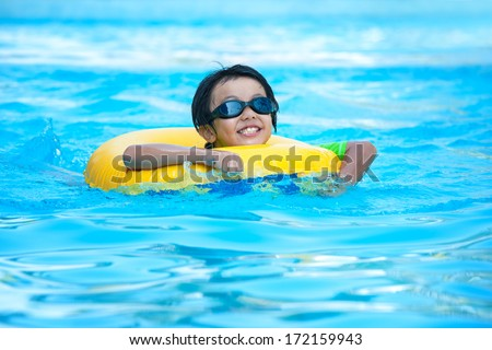 Asian boy in tube learning to swim - stock photo