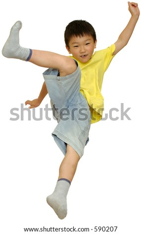 Asian boy jumping on bed doing high kick on white - stock photo