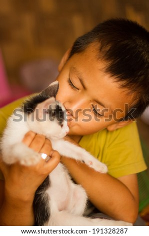 Asian boy kissing a cat. - stock photo