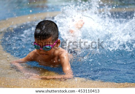 asian boy learning to swim in the rim around pool. Swimming lessons first step. - stock photo