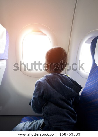 asian boy looking outside of airplane window - stock photo