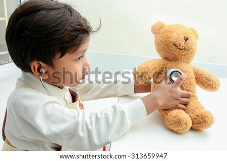 Asian boy play with bear  in the room. - stock photo