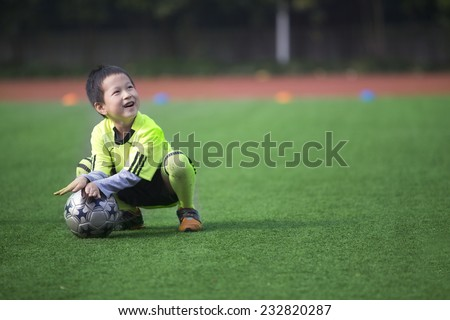 Asian boy playing football with happy - stock photo