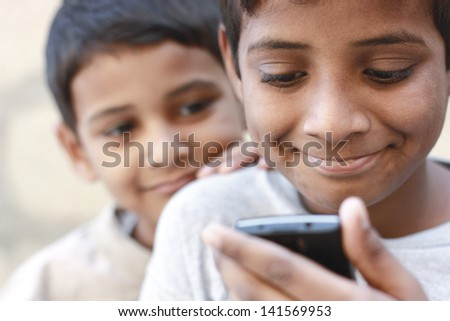 Asian boy playing on mobile phone and the brother looking on phone - stock photo