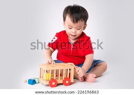 Asian boy playing with the small colorful wooden car. Little boy playing with cubes, smiling. - stock photo