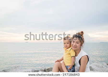 Asian boy pose on the beach with his mother, stock photo - stock photo