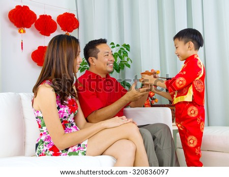 Asian boy presenting tea to his father during chinese new year - stock photo