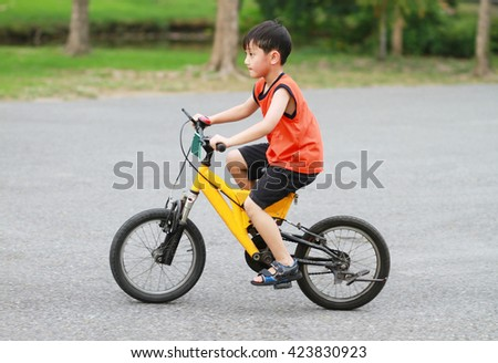 Asian boy riding bicycle in the park - stock photo