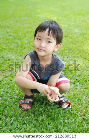 Asian boy smiling on green grass field  - stock photo