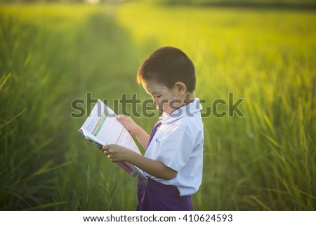 Asian boy standing reading the field,Children's books - stock photo