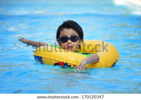 Asian boy swimming with tube - stock photo