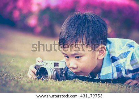 Asian boy taking photo by vintage film camera on blurred nature background at the day time. Adorable child enjoying at park. Outdoors. Vintage picture style. - stock photo