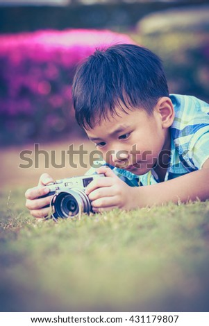 Asian boy taking photo by vintage film camera on blurred nature background at the day time. Adorable child enjoying at park. Outdoors. Vignette and vintage picture style. - stock photo