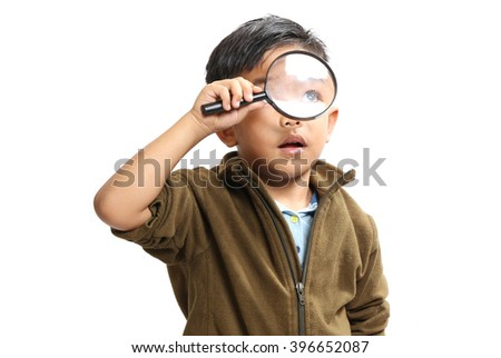 Asian boy using a magnifying glass on a white background. - stock photo