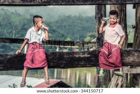 Asian boys talking on a can phone - stock photo