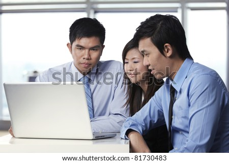 Asian business colleagues working around a laptop - stock photo