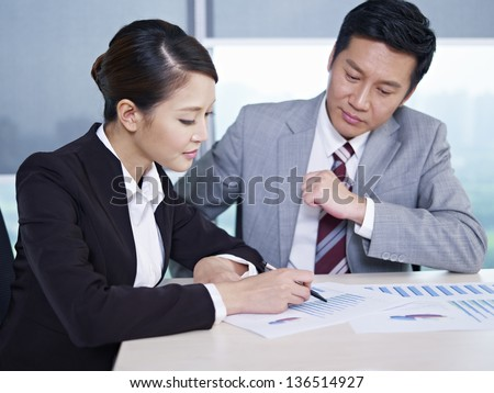 asian business executives discussing business in office; focus on the woman. - stock photo